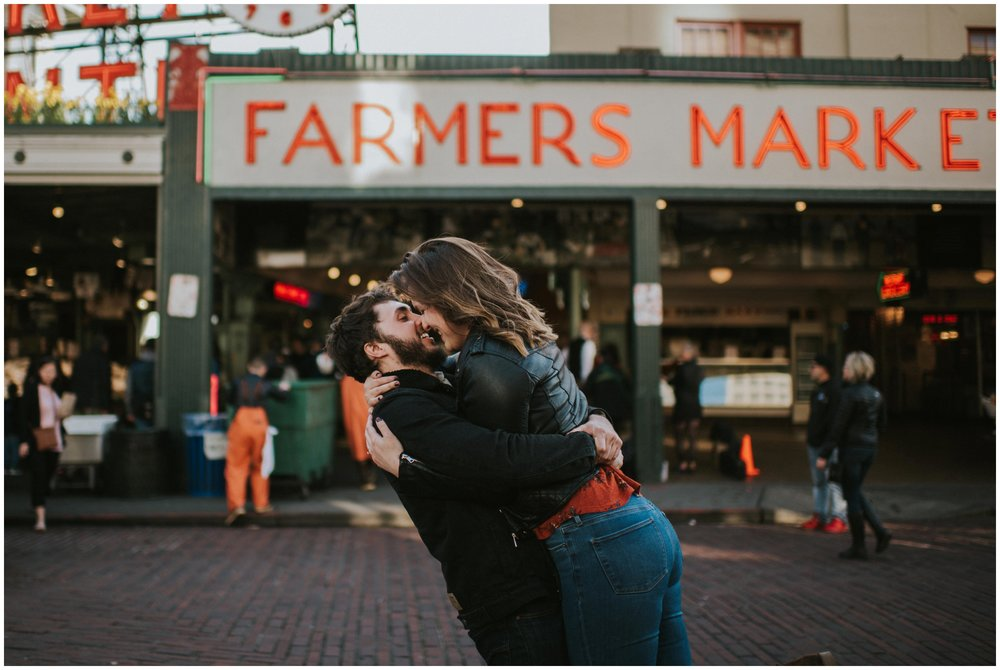Couple snuggling in the street at Pike Place Market  | Seattle Engagement Photographer www.riversandroadsphotography.com