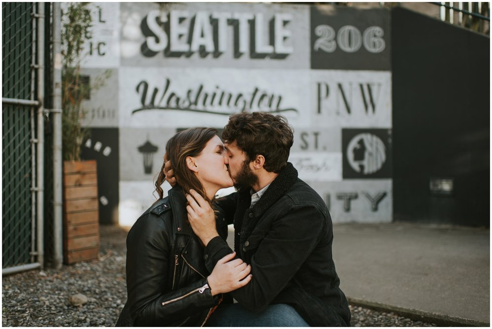 engaged couple kissing in front of graffiti wall  | Seattle Engagement Photographer www.riversandroadsphotography.com