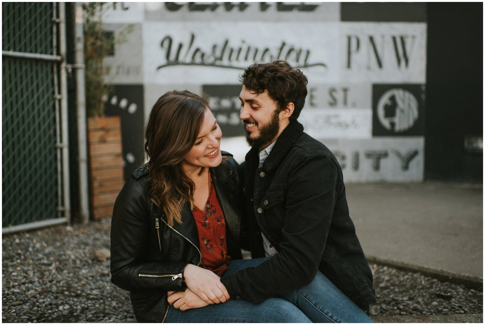 Cute couple posing in front of graffiti wall downtown  | Seattle Engagement Photographer www.riversandroadsphotography.com