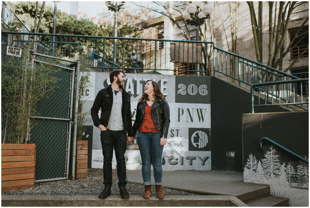 engaged couple genuinely laughing at graffiti wall downtown  | Seattle Engagement Photographer www.riversandroadsphotography.com