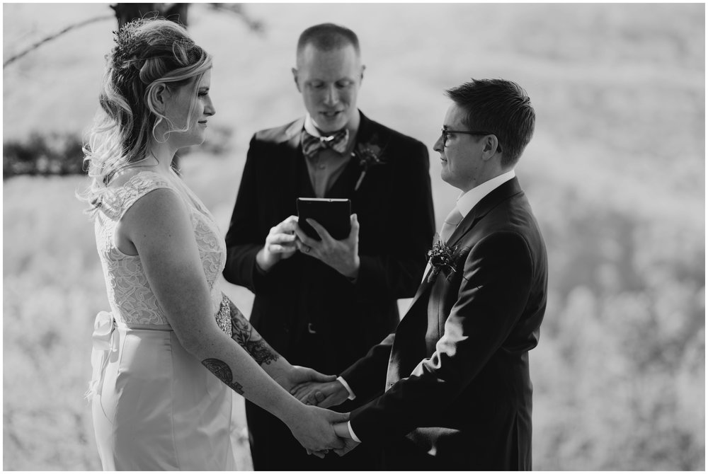 black and white image of couple holding hands while getting married Roanoke Mountain Elopement Photographer |www.riversandroadsphotography.com