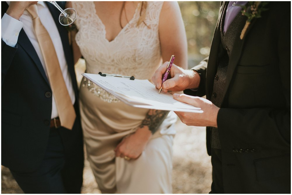 Officiant signing the marriage license after elopement | www.riversandroadsphotography.com