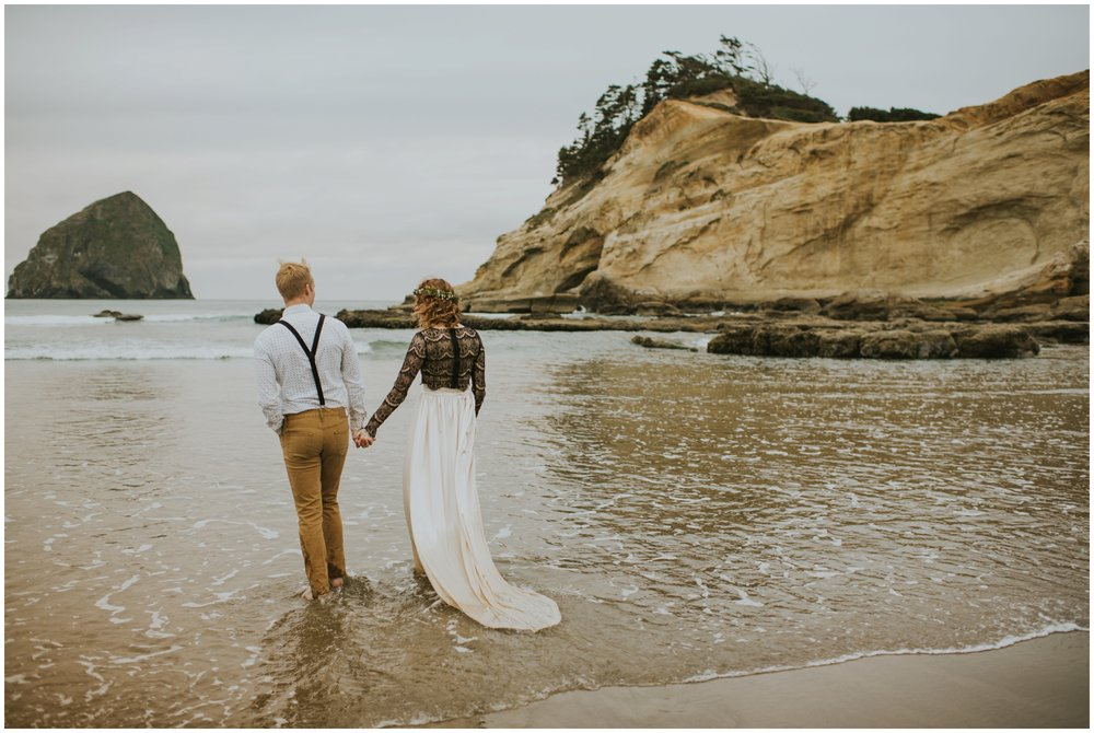 couple walking into the ocean in pacific city oregon