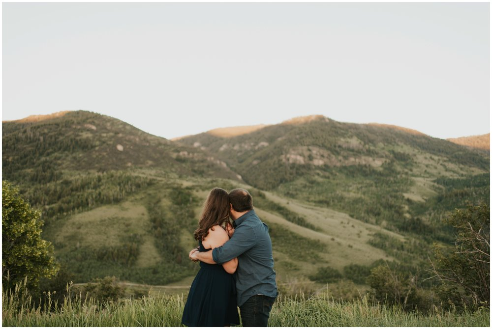 couple cuddling looking at the mountains in utah. Logan Utah Engagement Session