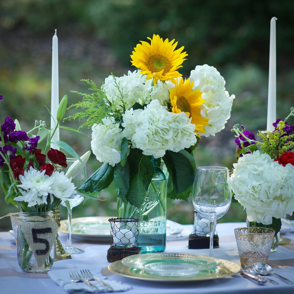 "FARM   The Farm package is perfect for any wedding in a barn, on a farm, or at any outdoor venue.  This package will add rustic charm and texture in any season.      Each table includes:        - 1 large (10"") blue mason jar vase (5 total)       - 2 clear regular size mason jar vases (10 total)       - 2 eclectic, brass candlesticks (10 total)*       - 3 chicken wire votives (15 total)       - 3 unscented white candles to go into the votives (15 total)       - 3 square, barnwood votive chargers (15 total)       - 1 burlap table number tag (5 total)**        -  1 large spool of twine for wrapping jars (1 total)   Other included items:        - 1 package of 5 handmade rustic signs (welcome, ceremony, reception, cocktails, and restrooms)       - 2 wooden farm crates        - 3 rustic buckets (for flowers at the welcome table, buffet or dessert tables, and beverages or ice at the bar)       - 1 strand of multi-colored paper Mexican wedding flags (12-15' long)       - 2 vintage bottles for flowers in restrooms       - 2 clear glass votives for restrooms       - 2 scented candles to go into the votives in restrooms  *Candlesticks do not always come in matching pairs but we ensure they look good together.  **If you order more than one package, we will adjust the numbers and price accordingly.  ***Flowers are not included."