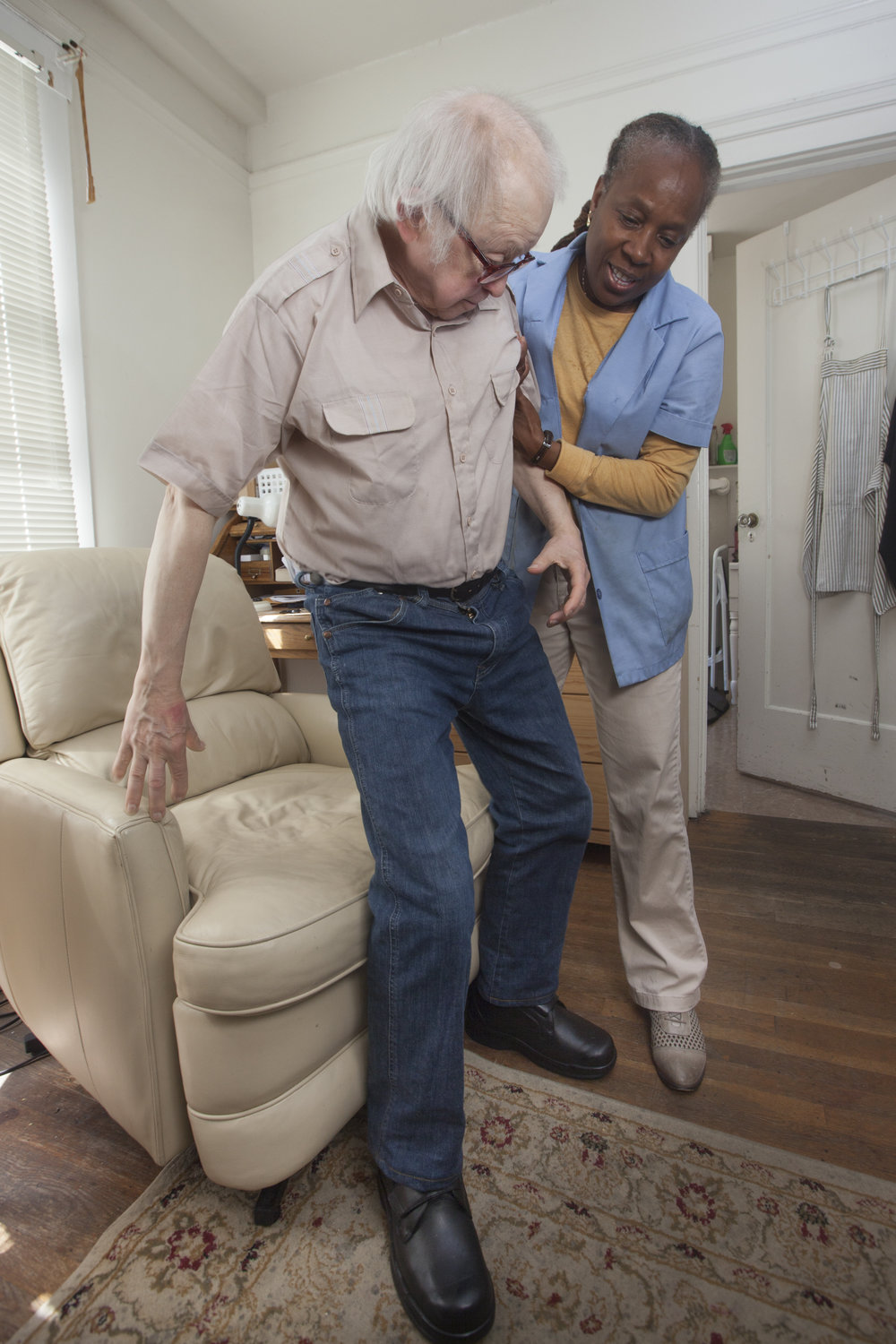 A personal care assistant help a man out of a reclining chair.