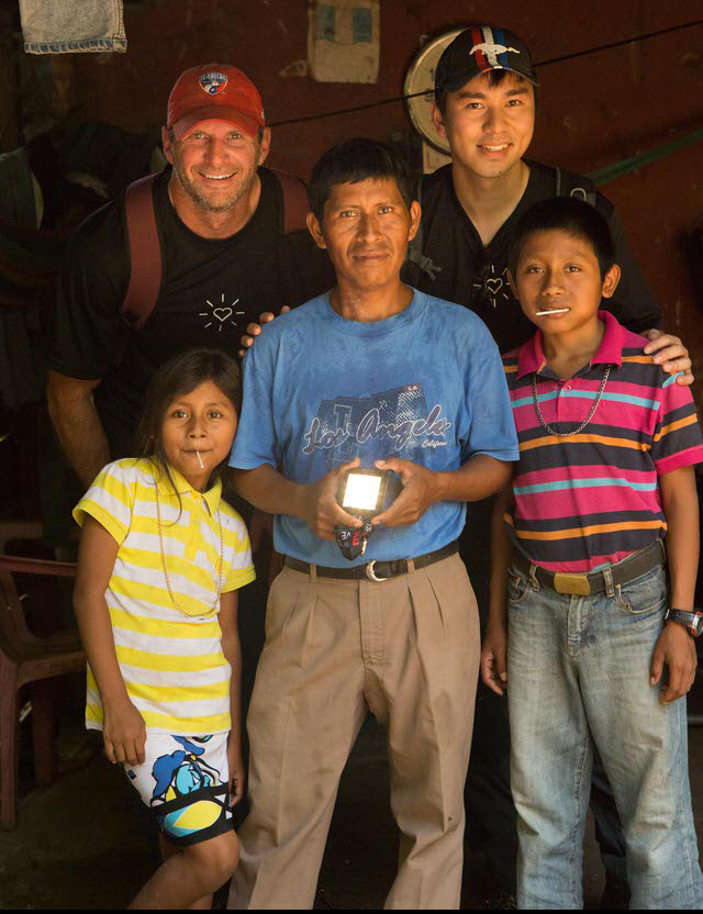 Scott Etheridge and Thomas Chung pose with a father and his children.