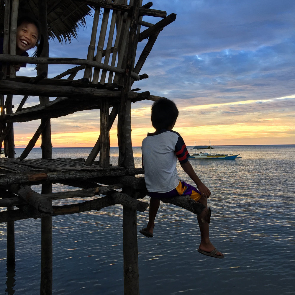 Young boys wait on the pier for returning fishermen at the end of the day on Ilin Island.