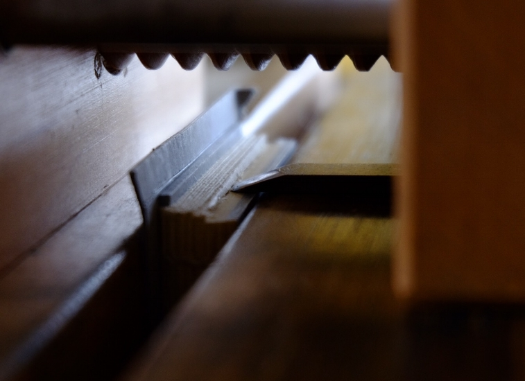 Here is a detail of the business end of the plough. The blade is depicted mid-cut as it makes a pass along the half-trimmed head, or top edge, of the book. As the wooden screw is turned (just visible at the top of the image), the blade progresses across the width of the book less than a millimeter each pass, trimming just a few pages at time but resulting in a perfectly smooth edge.