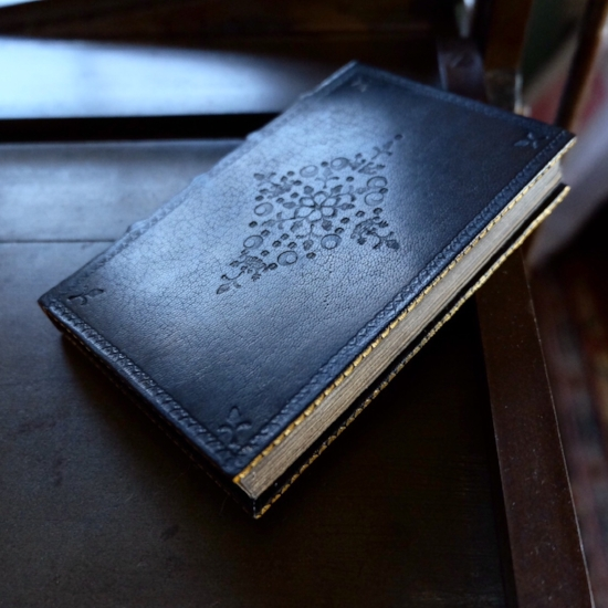 A commonplace book bound in black goatskin with both gold and bind tooling. The lozenge shaped decoration in the middle of the cover is executed using four different tools.
