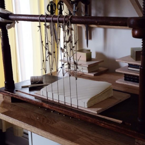 Sewing on six raised cords. These cords are key components of the finished book's structure and aesthetic, as they will eventually result in the raised bands on the spine of the finished volume.
