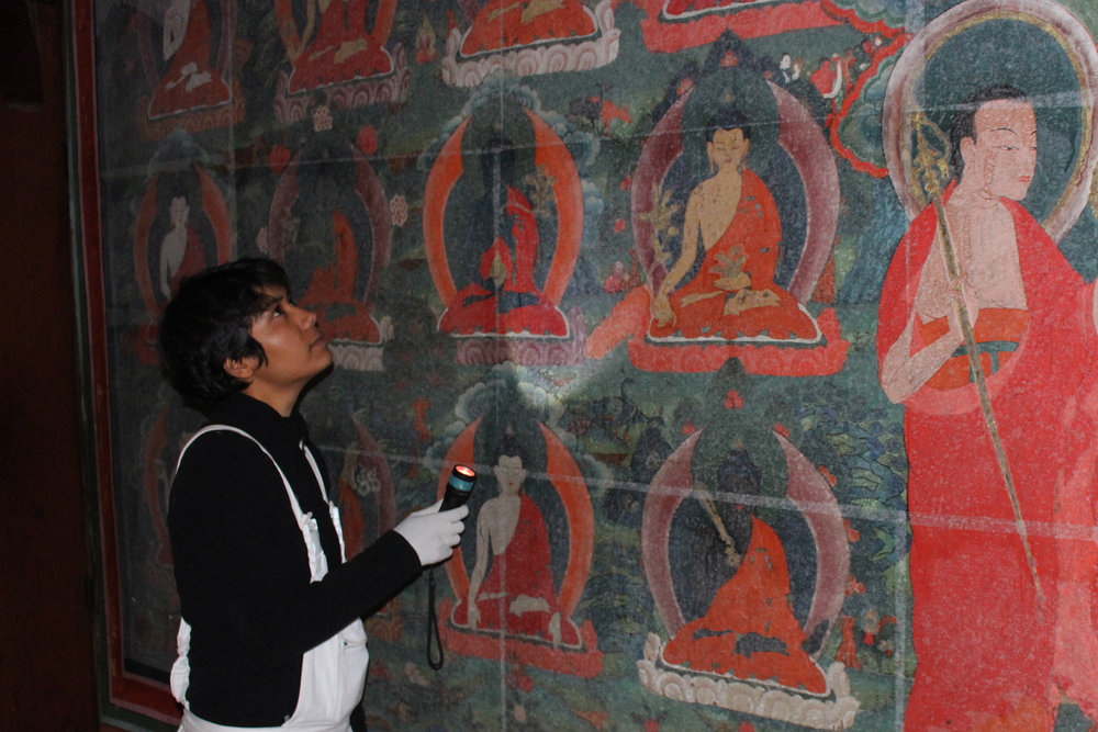 Kalpana uses a raking light to see the topographical information of the painted surface at the Tango Monestry, Bhutan.