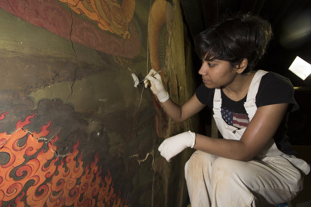 Kalpana temporarily stabilises a fragile fragment with gauze and cyclododecane at the Tango Monestry, Bhutan.