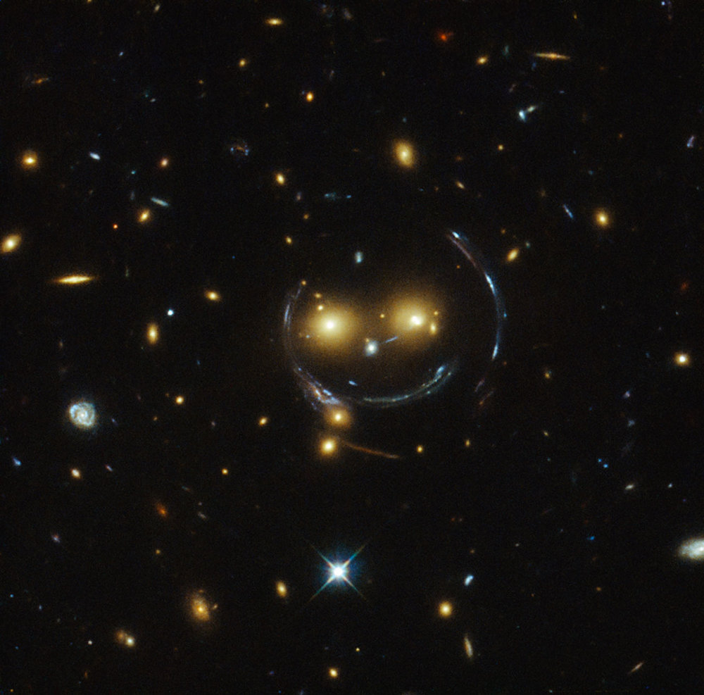 The galaxy cluster  SDSS J1038+4849 , which shows the distortions of background galaxies caused by gravitational lensing.  Photo Credits: NASA/ESA Hubble Space Telescope.