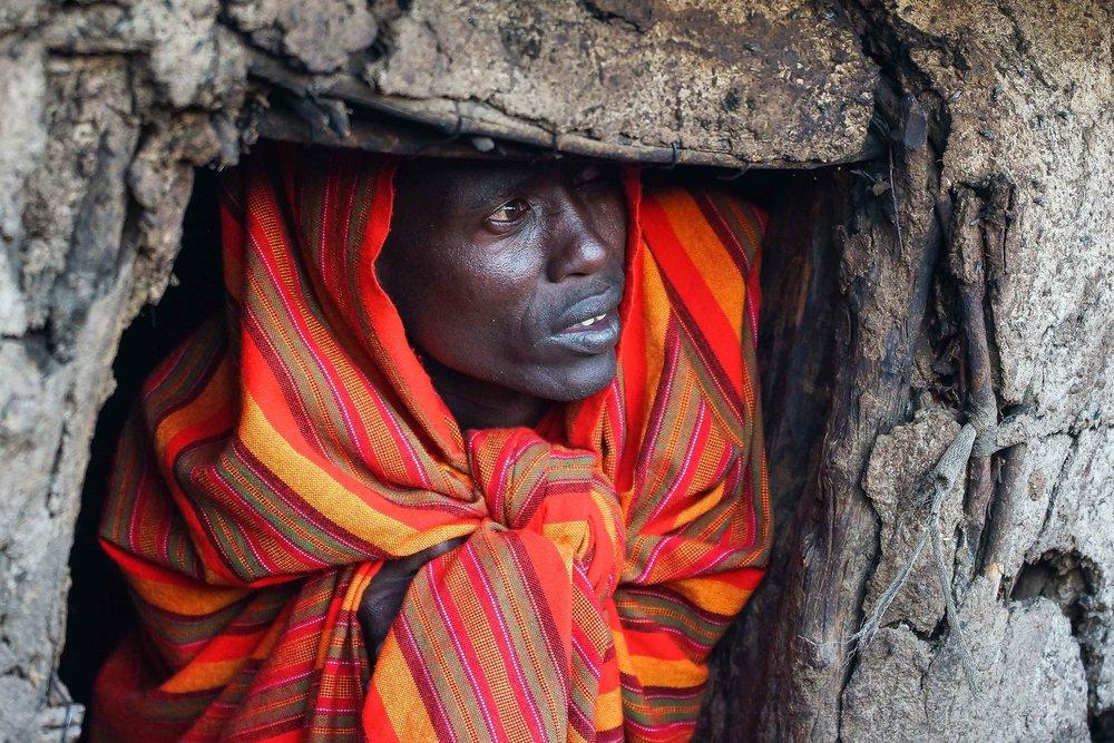 A Maasai man looks through his Inkajijik (house) into the setting sun, in a village on the outskirts of the Mara. Oloolaimutia, Kenya - August 17 2014.