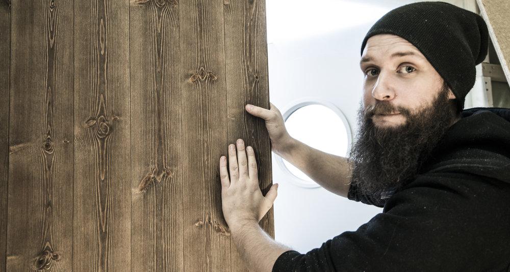Håkon Grytvik får på plass panelveggene i hytteanekset.