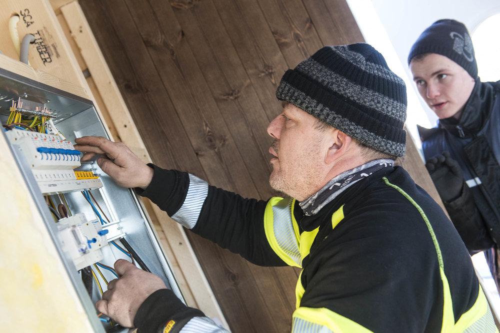 Installatør Håkon og lærling Stian i ferd med i installere og teste det nye sikringsskapet som står i den nye hytta på Dolmøya.