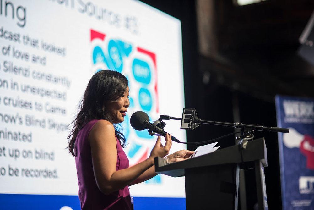 Kristen Meinzer presenting on stage behind a podium