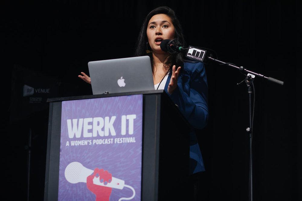 Megan Tan presenting on stage behind a podium