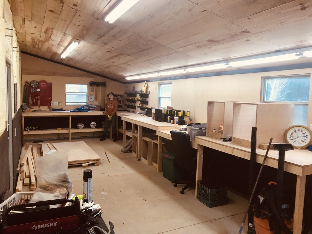 "Workshop - Inside   The workshop is still a work in progress that started in 2018. The walls that have been finished above the work benches are PureBond finish grade maple plywood. The work bench tops are 3/4"" finish grade maple plywood and then you can see the dark mahogony colored trim and shelves. The cabinet boxes are meant to hold drawers that will form a miter saw station. LED lighting and full power throughout this space. The ceiling was finished with pine boards that we cut from pines that fell in a storm several years ago. Again, all of the wall coverings have full spray-foam insulation behind them so you could add a heating/cooling unit and have the space fully conditioned."