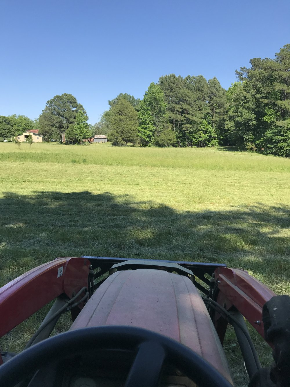 Taking a break from making hay. This is a view from the side pastures towards the back of the workshop.