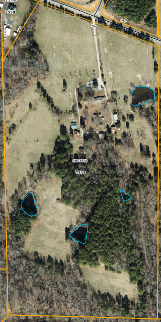 Aerial View - This is the overhead view of the farm. You can see the entry from the road. The gate is far enough off the road so that multiple cars or tractor-trailers can pull into the driveway and stop at the gate without being out in the road. You can see the three larger ponds indicated here. There is a smaller swale in the woods that stays year round but I wouldn't really call it a pond.The driveway enters from the road and wraps all the way around the house and farm yard as you can see. Most of the usable buildings on the farm are accessible directly from the drive. The perimeter fence wraps all the way around the farm boundary (about 2 miles total) and crosses all the creeks with creek crossings. It will keep your livestock and dogs in and predators out. We let our livestock dogs roam the entire farm because they can only go to the boundaries. There is also a 3 wire fence that separates the farm from the driveway and farmyard/house. This allows you to keep your animals out in the pastures without having to worry about them getting through the gate when someone opens it…or on the porch if they happen to be a porch dog!You can see the pines in the middle of the farm. This area used to be pasture according to our neighbor who grew up on the farm. It now is covered with 50-60 year old pines according to the forest service. The sides and back ridges are covered with hardwoods and a few very old pines that the forest service aged to over 110 years old. Lots of red oak, white oak, hickory, poplar, beech, maple, etc. The entire farm has paths to make all of these places easily accessible.