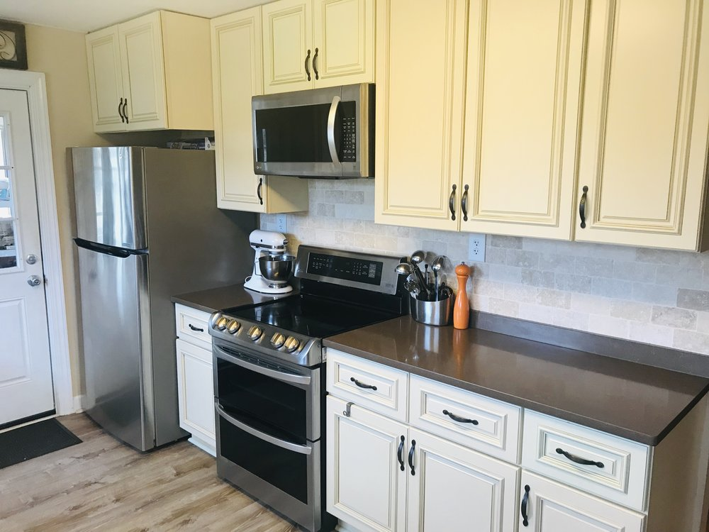 Stainless LG refrigerator/freezer, double oven, range cooktop, and microwave. Stainless KitchenAid dishwasher not shown but shown in other photos.