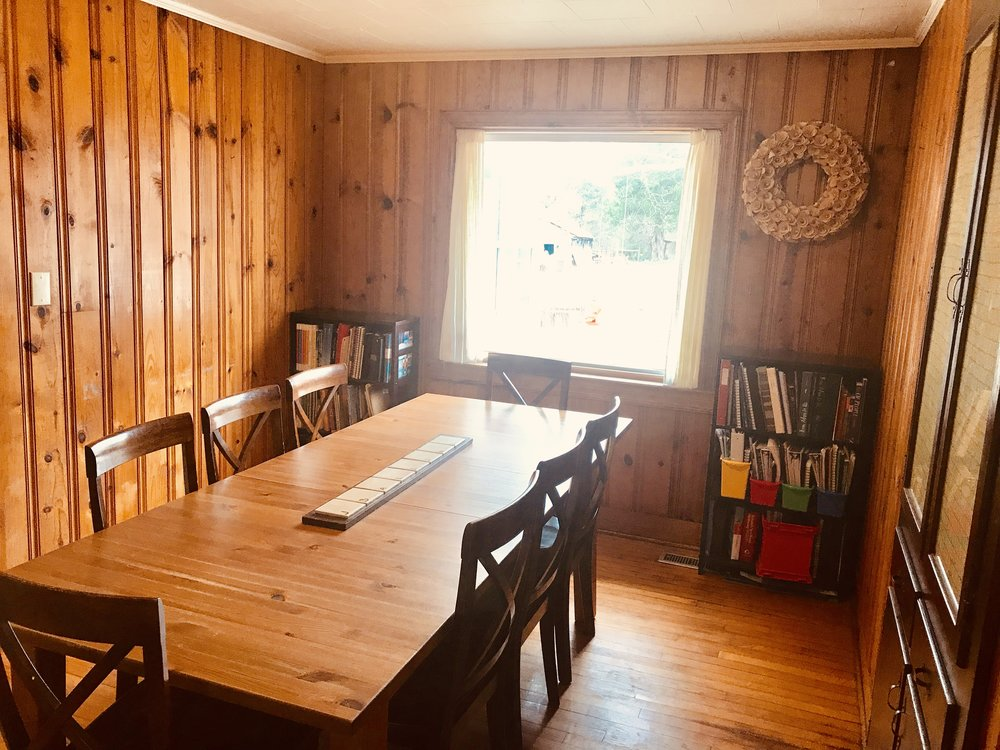 This is the dining room. To the right is a built in glass front china cabinet that we use to store homeschool supplies. The walls are pine and were cut from trees right here on the farm according to our neighbor who built the home with his father. We have considered taking them out and installing sheetrock for an updated look, but there is a lot of character with the way they are so we've left them alone.