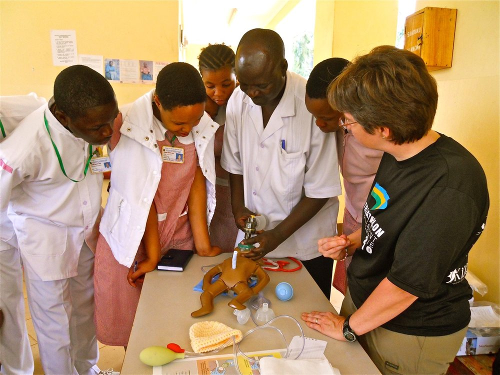 "Dr. Diane Gerlach supervises a group of medical professionals learning the ""Helping Babies Breathe"" neonatal resuscitation technique in Tanzania."