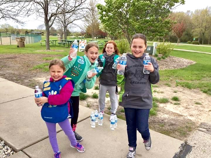 Enthusiastic Girl Scouts distribute water to Walk/Run participants