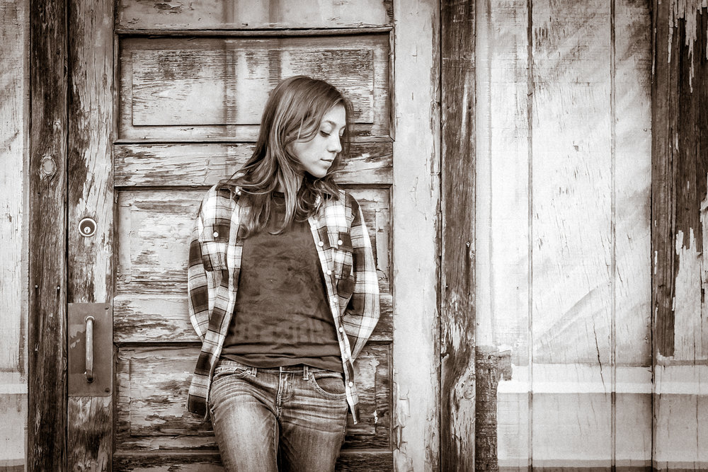 Portrait-HIgh-School-Seniors-girl-in-flannel-serious-against-wood-door-190.jpg
