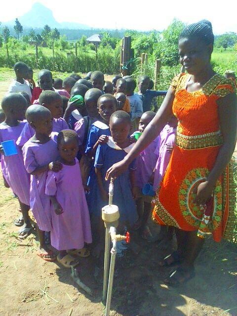 Here are the kids and teacher enjoying the brand new water line!  No more fetching and it is clean piped from the city!