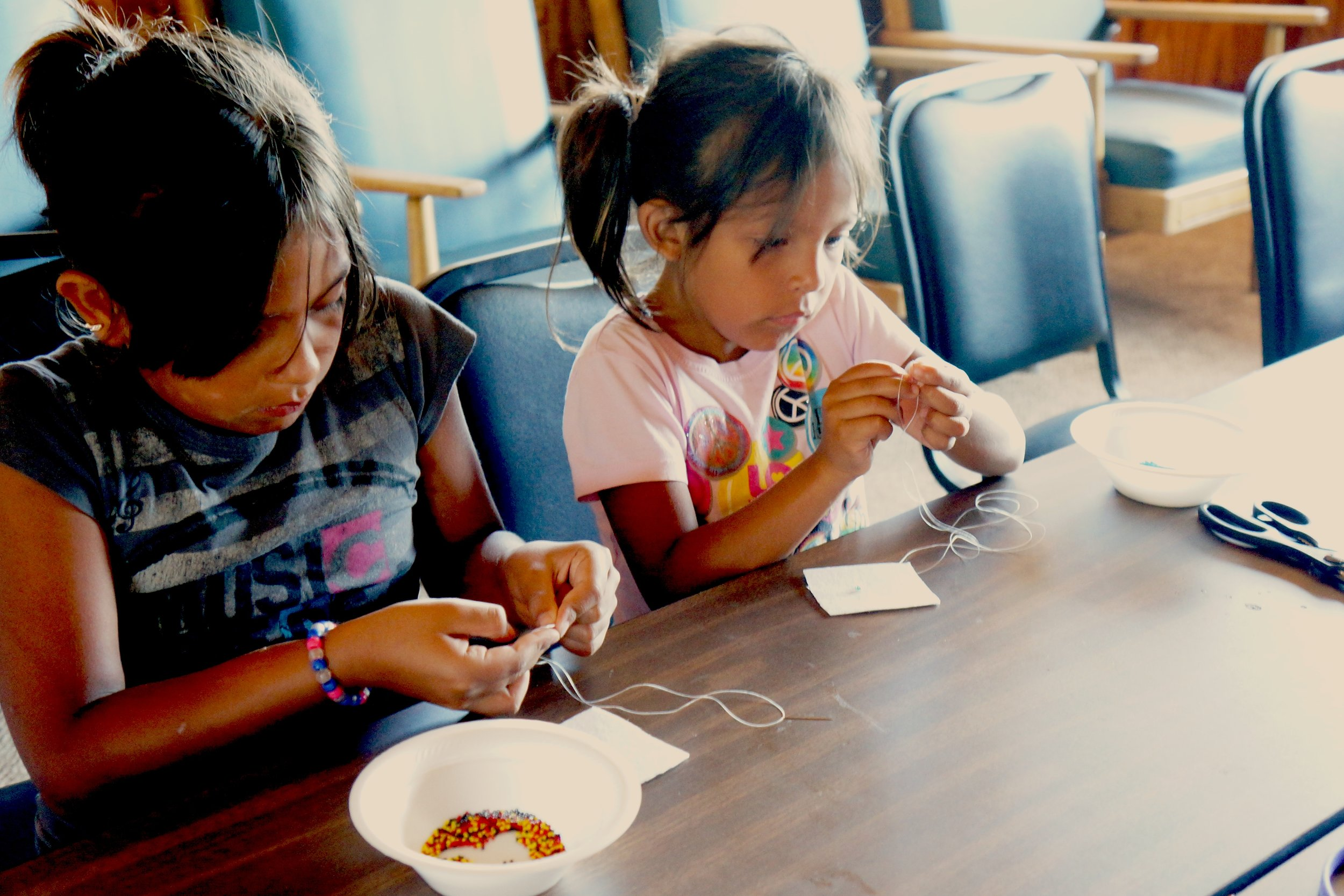 Zoey, 6 and Sophia, 7 during ANCC Summer Session, 2012. Beading simple objects, like a medallion or a hairband.