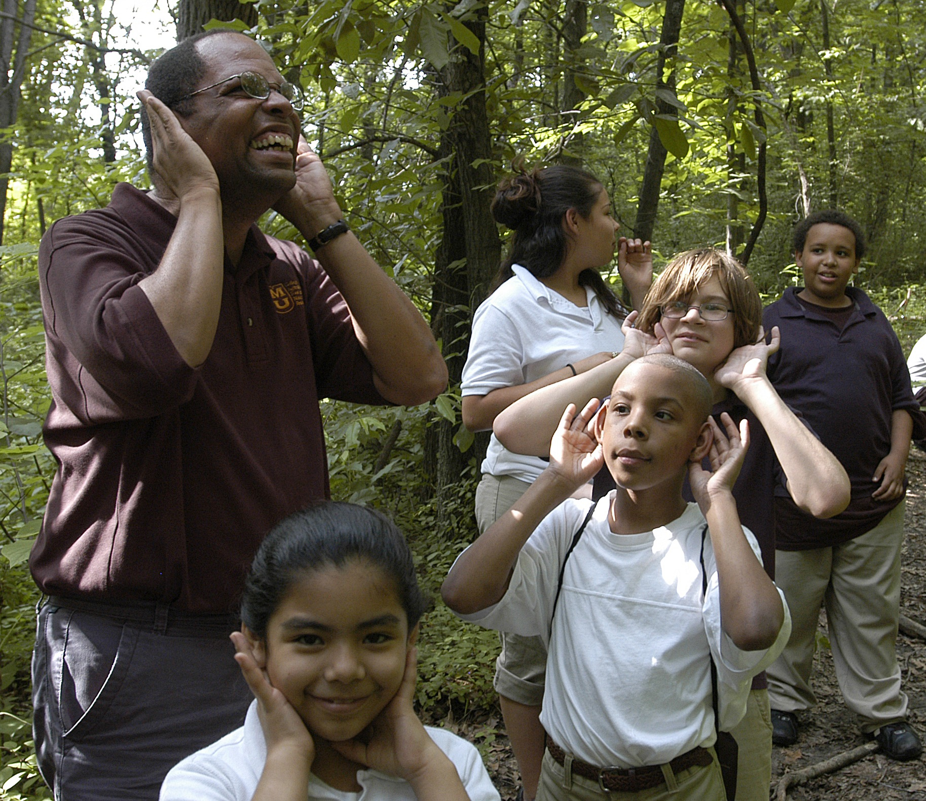 Charles Nilon encourages a group of Kansas City area school choldren to listen to the sounds they hear on a walk along a nature trail near their school. Photo by Steve Morse