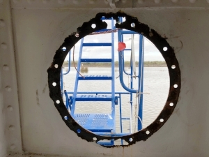 Porthole on the starboard side. Metal trim is thin and corroded.