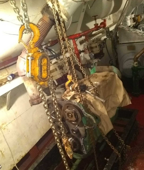 """Lifting the Detroit Diesel. It has to be """"walked"""" down the corridor then up to the second floor of the engine room."""