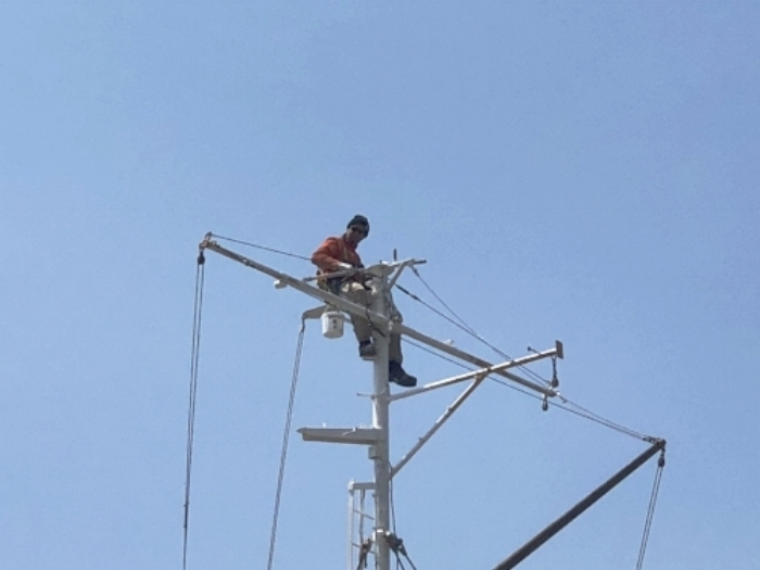 Leo pressure washes the aft mast in preparation for painting.