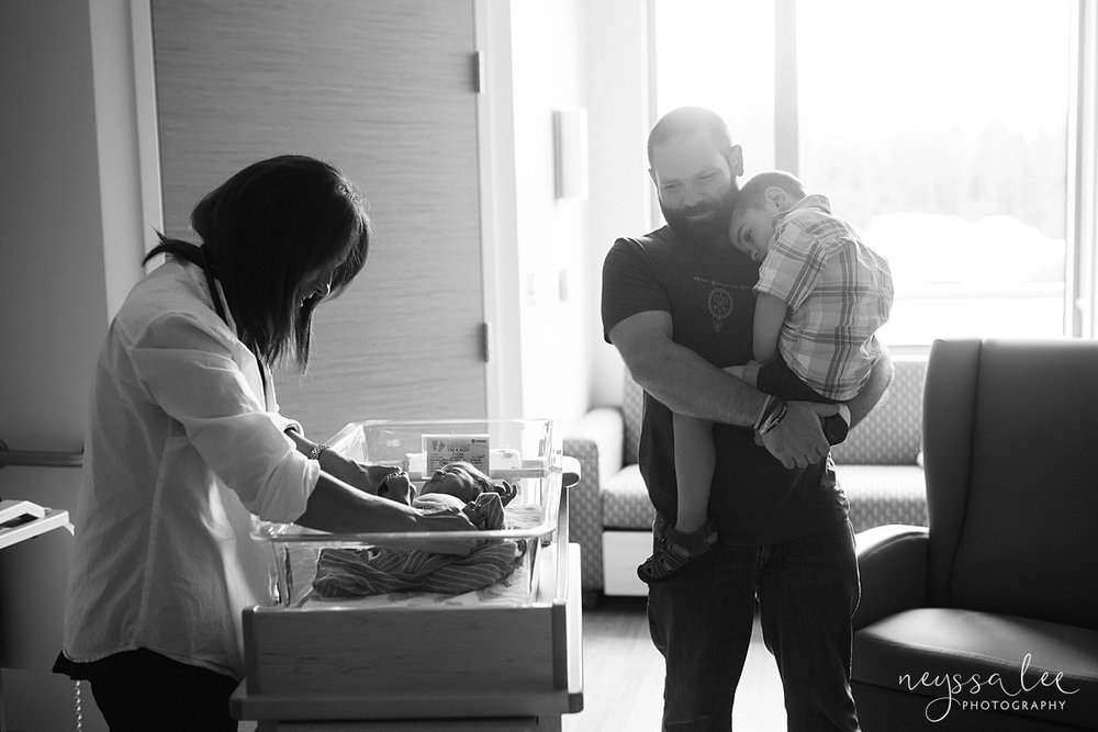 unsure of fresh 48 photos, issaquah fresh 48 photographer, Neyssa Lee Photography, Father and Son watch doctor give newborn checkup