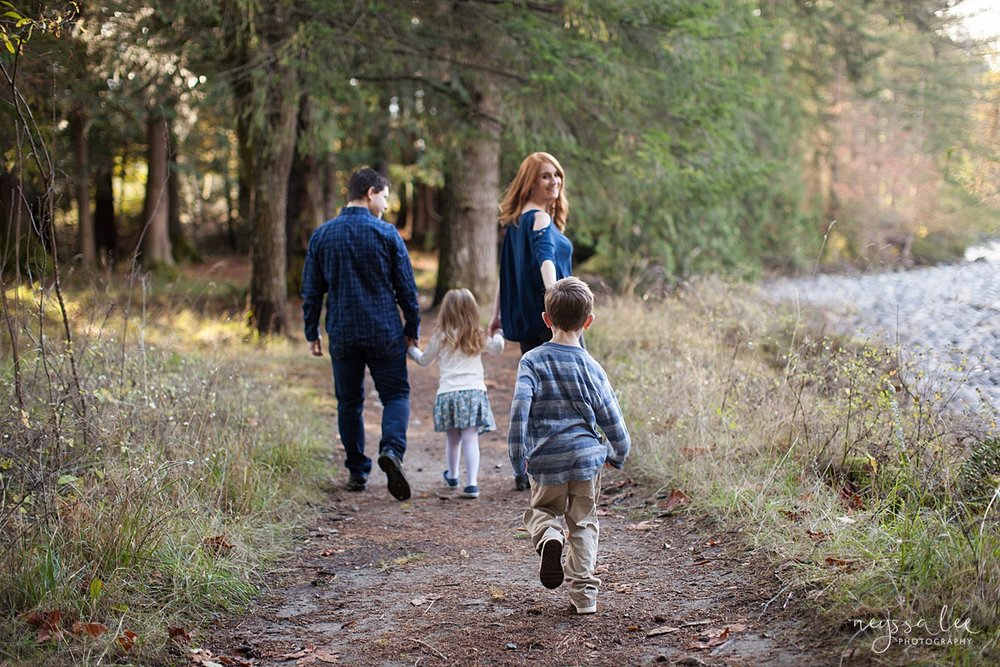 Neyssa Lee Photography, Photo of family of son catching up to family walking together in the woods, lifestyle family photography, Seattle Family Photographer