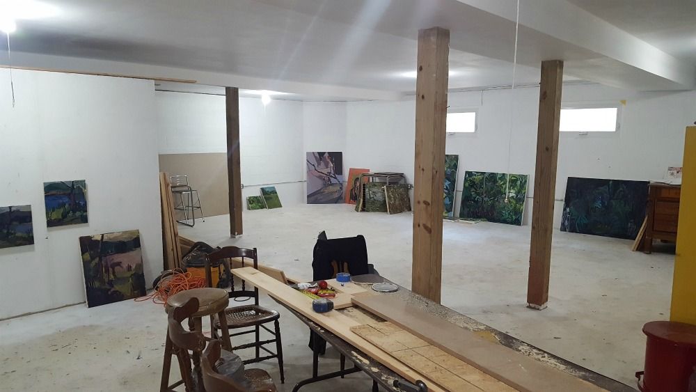 The Artist Cottage work space after artists had packed up all their belongings in 2016. The artwork shown is being stored preparation for an upcoming exhibit. A divider wall is visible at left. This space may not be available in 2019. New studios are being developed.