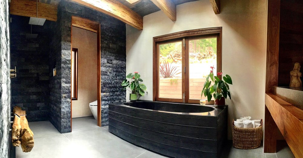 Carmel Highlands Master Bath. The whole house has exposed PSL beams, barn wood ceilings, white plaster walls and walnut accents. Poured in place board-formed black concrete bathtub, custom 5 foot concrete sink he made before he started the house (not fully pictured), stone walls, double shower heads, and 150 lb Big Sur driftwood log bench mounted to the wall by stainless steel fasteners.