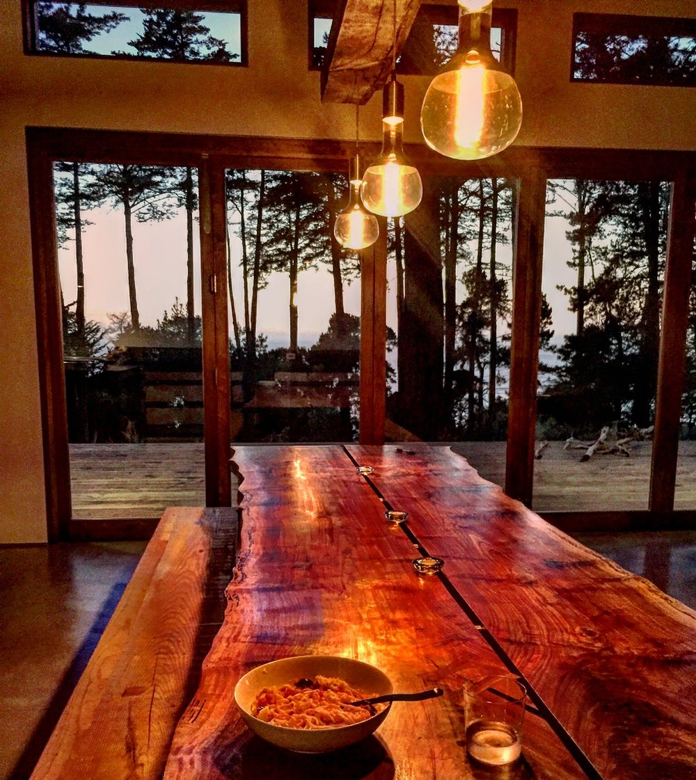 The 10 foot walnut slab dining room table we made.  Poured concrete base not pictured. View of the ocean at sunset. Huge bifold doors open up onto the big front deck.  Deck made out of Pakari, a new thermally modified wood.