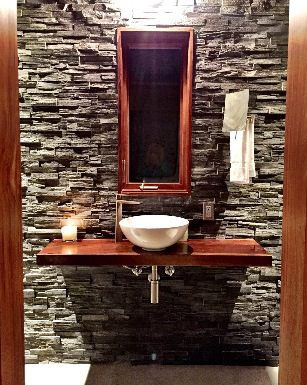 Guest house bathroom vanity. Slate walls, walnut slab and white vessel sink.