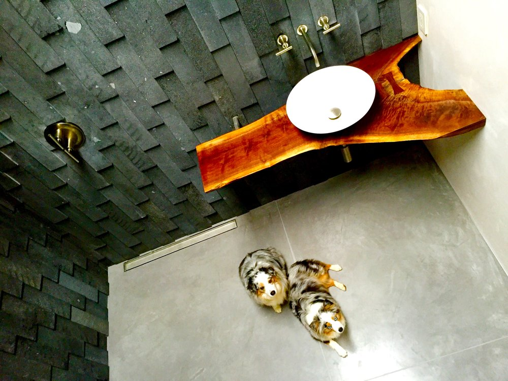 Middle glass-free bathroom.  Volcanic rock walls, walnut slab counter top, white vessel sink, concrete slab floors.