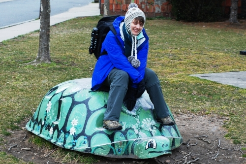 Tara riding a turtle, which happens to be her favorite animal.