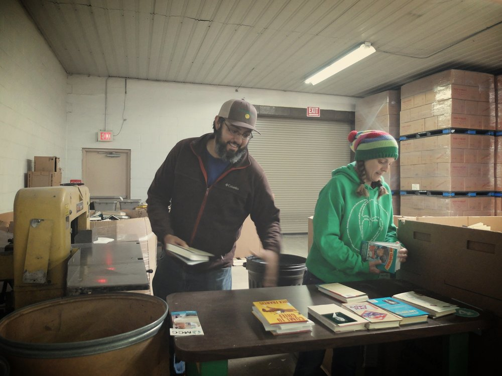 John-Michael (left) and Tara (right) recycle books using a machine that cuts the spine off donated books, making it easier to separate the covers from the recyclable paper inside. (MCC photo/Laura Pauls-Thomas)