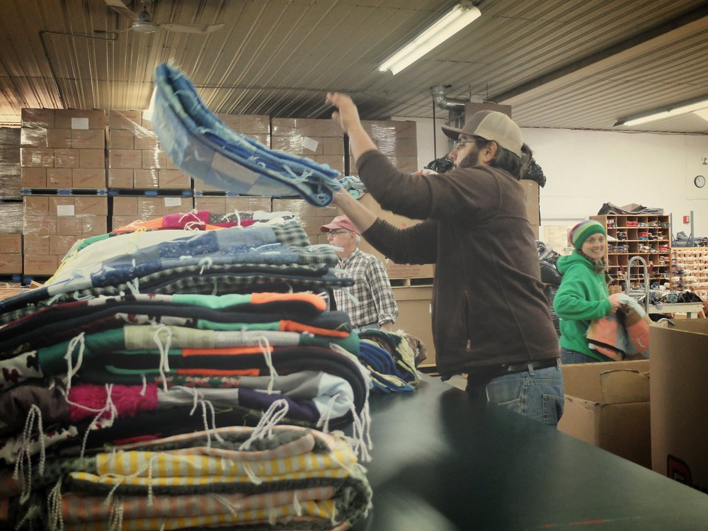 They also inspected comforters for quality assurance, then folded and baled the colorful, lovingly handmade blankets for shipment. All comforters that arrive at the MRC are created and donated by individuals and groups or sewn and knotted by volunteers there. (MCC photo/Laura Pauls-Thomas)