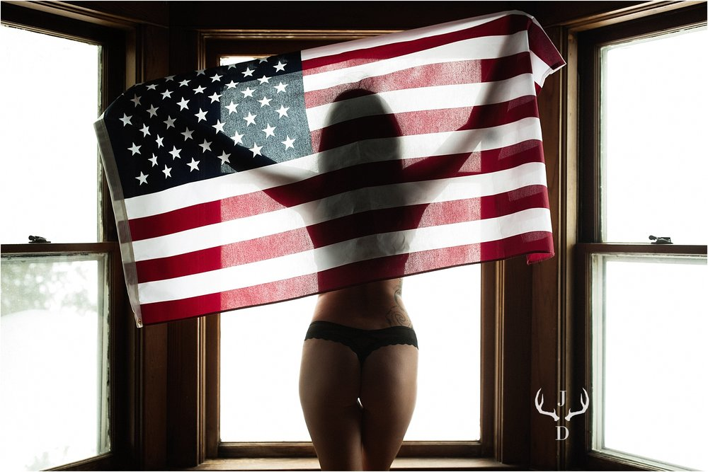 Silhouetted butt shot boudoir photo with an american flag for her military man.