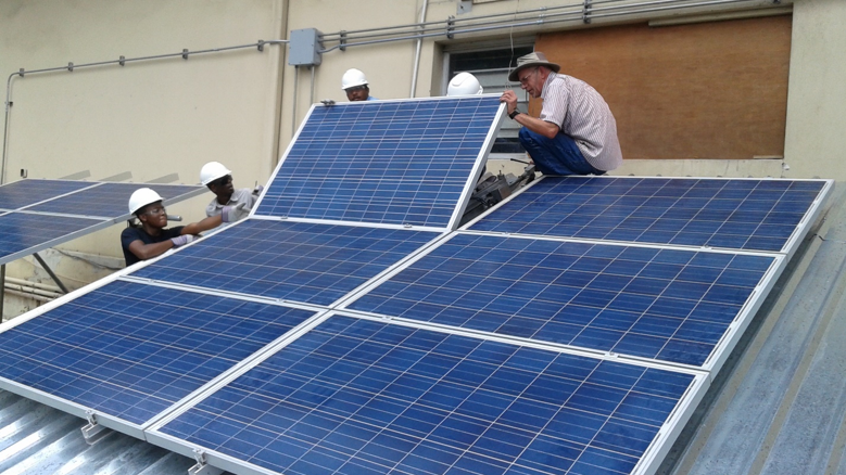 Brad and Haiti Tec instructors installing PV system on a mock roof as part of a hands-on Train-the-Trainers instruction