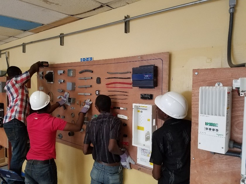 Haiti Tec teachers prepping the classroom with a display board.